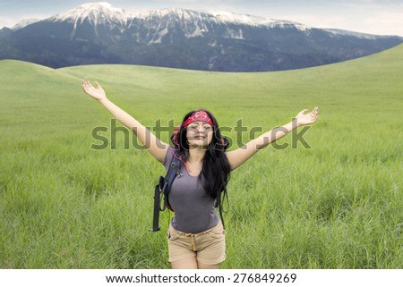 Portrait of beautiful woman hiking on the mountain and enjoy fresh air while stretching her hands - stock photo
