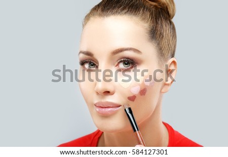 Portrait of beautiful woman holding make-up brushes.Putting makeup .Contouring.Make up woman face. Contour and highlight makeup.
