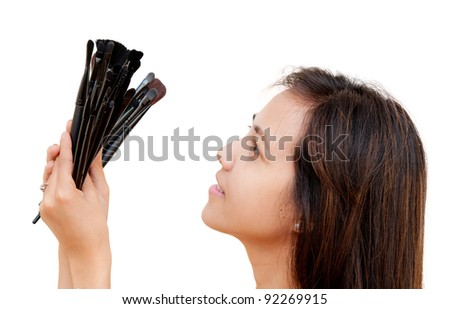 portrait of beautiful woman holding makeup brushes