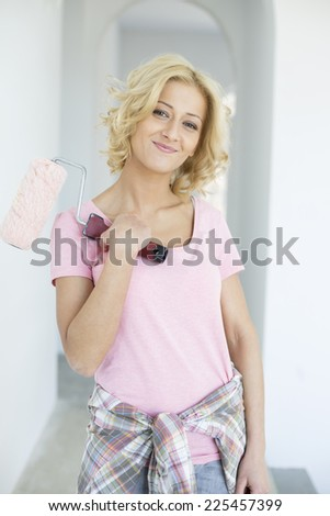Portrait of beautiful woman holding paint roller in new house - stock photo