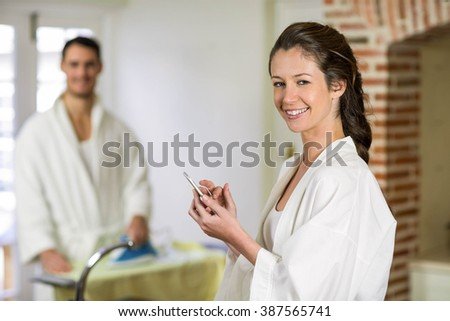 Portrait of beautiful woman in bathrobe sitting on kitchen worktop and typing a text message on smartphone while man ironing clothes behind her - stock photo