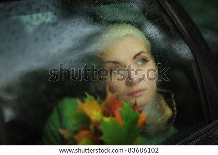 Portrait of beautiful woman in car looking out through wet glass. Closeup. - stock photo