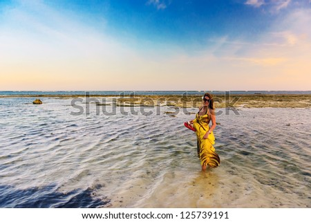 Portrait of beautiful woman in colorful dress walking through water on the exotic beach - stock photo