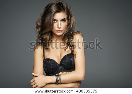 Portrait of beautiful woman in lingerie posing. Girl with long curly hair - stock photo