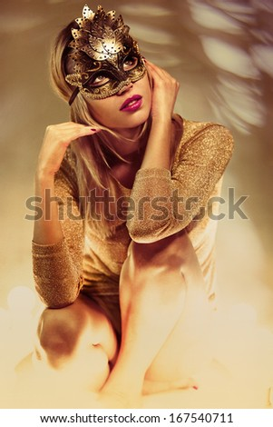 portrait of beautiful woman in mask with unusual ligt settings - stock photo