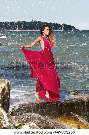 Portrait of beautiful woman in red dress at the sea beach - stock photo