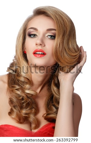 Portrait of beautiful woman in red dress doing up her hair. Wedding coiffure and make-up. - stock photo