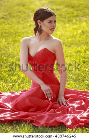 Portrait of beautiful woman in red dress in nature