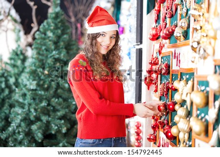Portrait of beautiful woman in Santa hat buying Christmas ornaments at store - stock photo