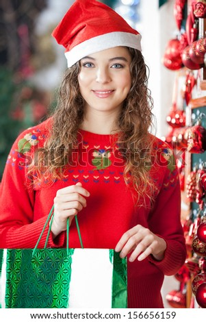 Portrait of beautiful woman in Santa hat carrying shopping bag at store - stock photo