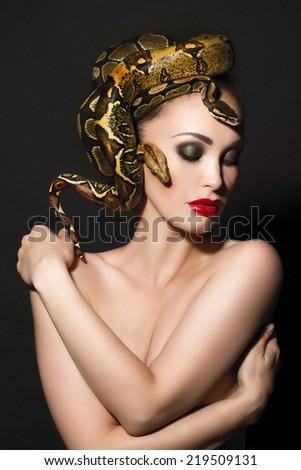 Portrait of Beautiful Woman in studio with dangerous snake - stock photo