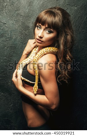 Portrait of Beautiful Woman in studio with dangerous snake