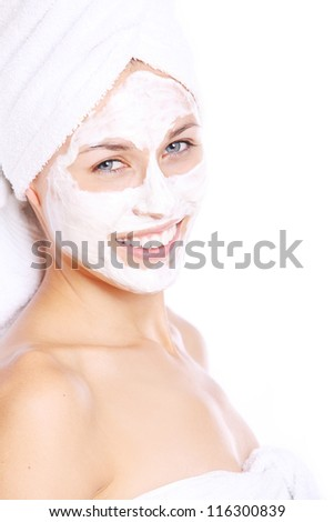 Portrait of Beautiful woman in towel with facial mask over white background - stock photo