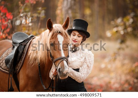 Portrait of beautiful woman in vintage stylized suit and top hat with a horse.
