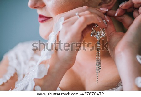 Portrait of beautiful woman in white dress. Bride with crown and wears earrings. Amazing make up. - stock photo