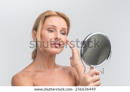 Portrait of beautiful woman looking at mirror. aging woman touching skin and looking at wrinkles - stock photo