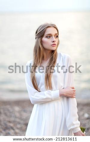 Portrait of beautiful woman near the water - stock photo