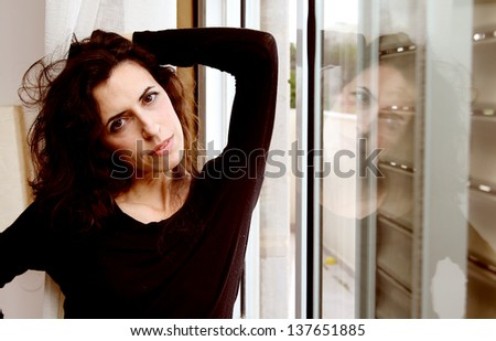 Portrait of beautiful woman near the window - stock photo