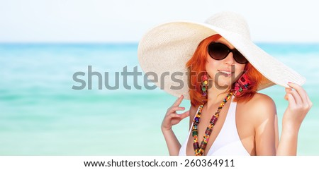 Portrait of beautiful woman on the beach, wearing stylish sunglasses and big hat, enjoying summer vacation on luxury sea resort, copy space - stock photo