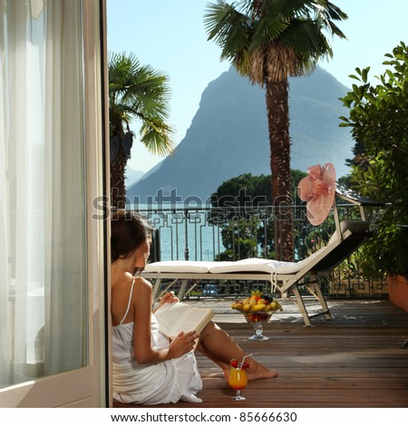 portrait of beautiful woman on the terrace of prestigious hotel.back view - stock photo
