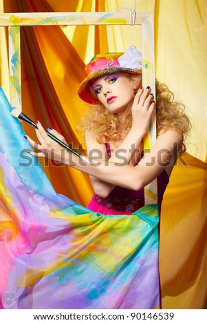 portrait of beautiful woman painter with paintbrush standing behind the easel with painted cloth on it - stock photo