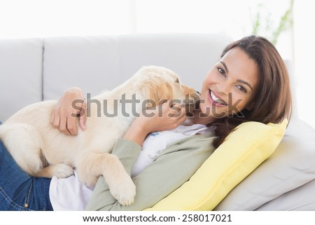 Portrait of beautiful woman playing with puppy while lying on sofa at home - stock photo