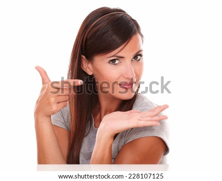Portrait of beautiful woman pointing to her left and holding her palm up while smiling at you on isolated studio - copyspace