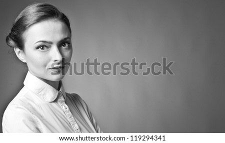 Portrait of beautiful woman posing on grey background - stock photo