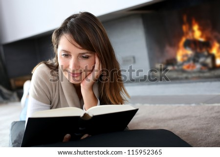 Portrait of beautiful woman reading book by fireplace - stock photo