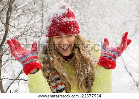 Portrait of beautiful woman screw up her eyes during play in snowball - stock photo