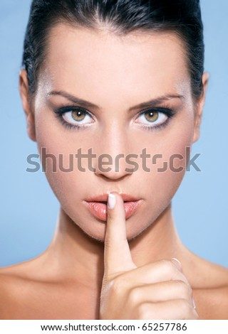 Portrait of beautiful woman, she doing quiet gesture, isolated on blue - stock photo