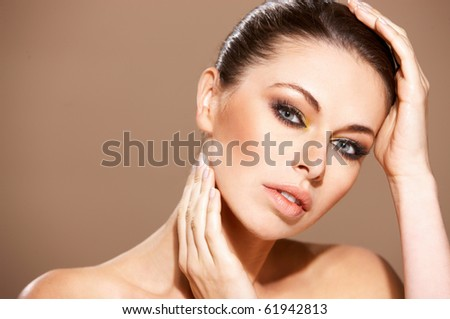 Portrait of beautiful woman she is doing neck massage isolated on beige - stock photo