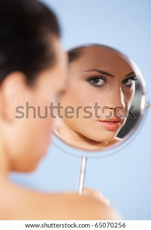 Portrait of beautiful woman, she is looking at the mirror, isolated on blue