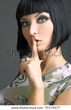 Portrait of beautiful woman, she's doing quiet gesture. Studio shot. Dark grey background. - stock photo