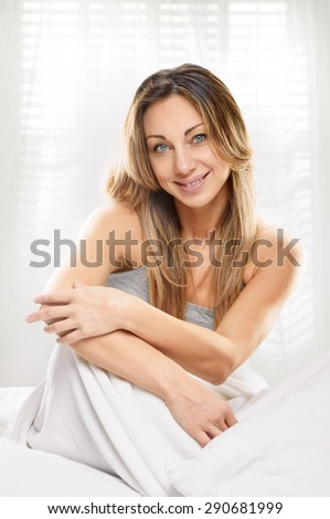 Portrait of beautiful woman, she sitting on white bed with window light background - stock photo