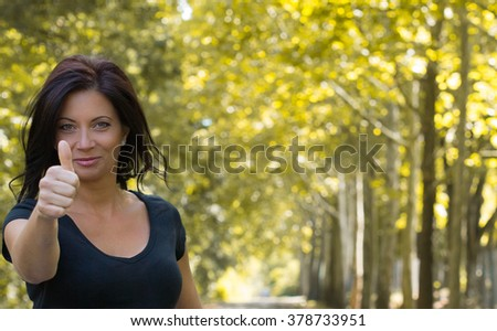Portrait of beautiful woman showing thumbs up sign - stock photo