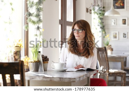 Portrait of beautiful woman sitting in coffee shop. - stock photo