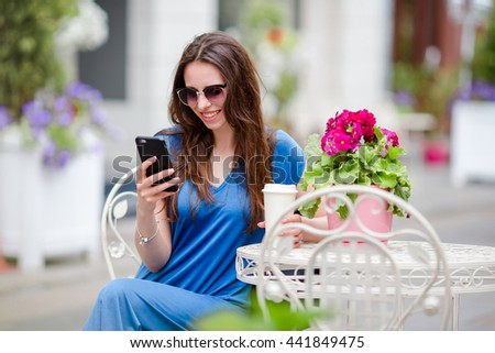 Portrait of beautiful woman sitting in outdoor cafe drinking coffee and using smartphone. Young girl looking instagram and drinking delicious sweet cappuccino. - stock photo