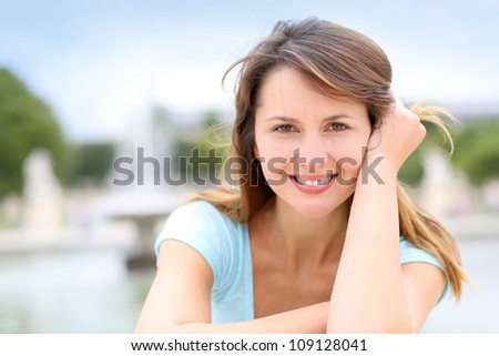 Portrait of beautiful woman sitting in park - stock photo