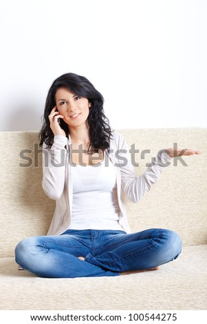 Portrait of beautiful woman sitting on sofa with mobile phone - stock photo