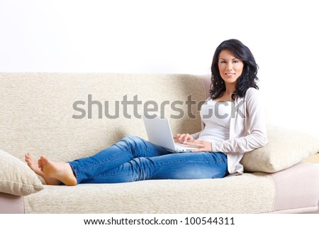 Portrait of beautiful woman sitting on sofa with netbook