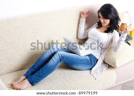 Portrait of beautiful woman sitting on sofa with netbook - stock photo