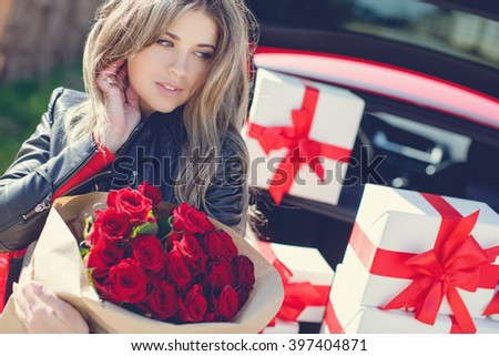 portrait of beautiful woman sitting with bouquet of red roses on car trunk full of gift boxes. holiday. happy woman. wrapped presents. luxury red car. happy sexy woman.  - stock photo