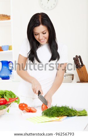 portrait of beautiful woman slice, cutting tomato in the kitchen, cooking, prepare  vegetable salad, happy smile