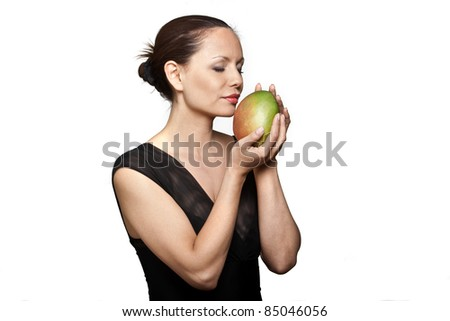 Portrait of beautiful woman smelling fresh mango with eyes closed in studio isolated on white background - stock photo