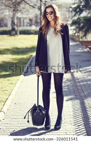 Portrait of beautiful woman smiling, wearing casual clothes, bag and sunglasses in urban background - stock photo