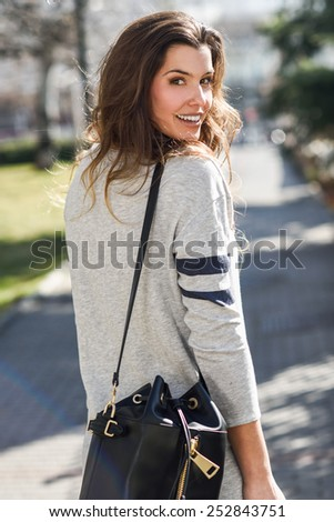 Portrait of beautiful woman smiling, wearing casual clothes in urban background - stock photo