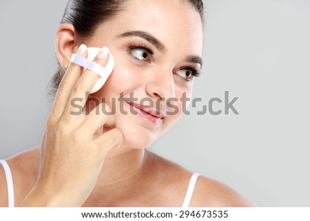 portrait of beautiful woman smiling while applying some powder using powder puff with copy space - stock photo