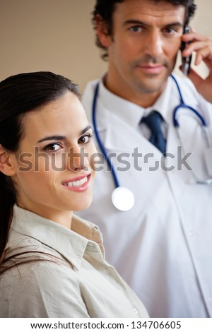 Portrait of beautiful woman smiling while doctor answering phone call in background