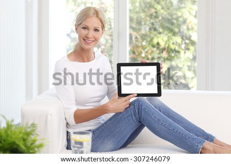 Portrait of beautiful woman smiling while sitting at sofa at home and holding hands white screen tablet.
